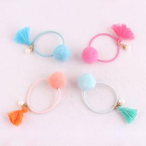 Child pink pom pom ponytail holder with tassels