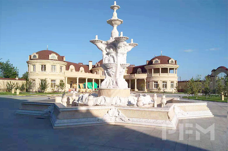 large outdoor beige marble stone water fountain